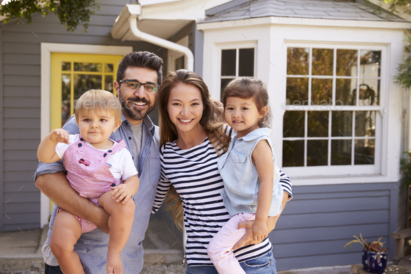 Portrait Of Excited Family Standing Outside New Home - Stock Photo - Images