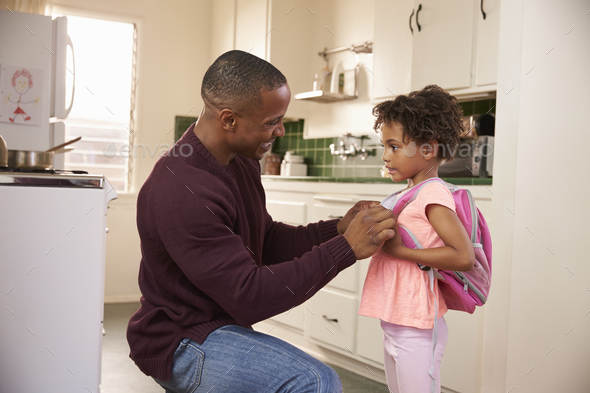 Father Helps Daughter With Backpack As She Leaves For School - Stock Photo - Images