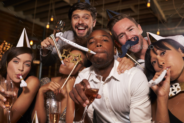 Friends having fun celebrating New Year at a bar, close up - Stock Photo - Images