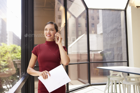 Smiling young white businesswoman on phone in modern office - Stock Photo - Images