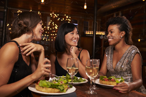 Three female friends eating dinner together at a restaurant - Stock Photo - Images
