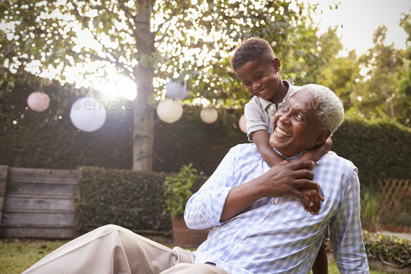 Young black boy embracing grandfather sitting in garden - Stock Photo - Images