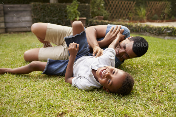 Black father and young son play lying on grass, low angle