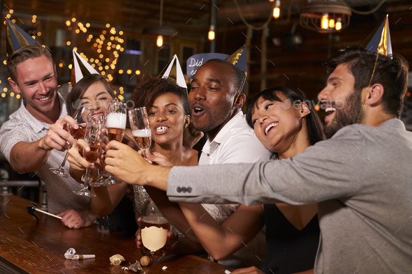 Friends toasting with champagne at New Year's party in a bar - Stock Photo - Images