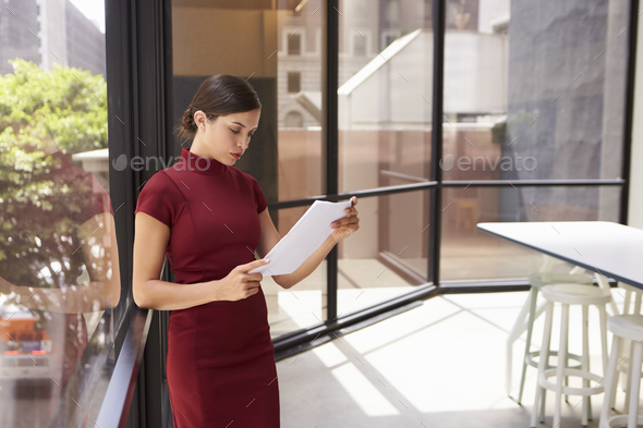 Young white businesswoman reading document in modern office - Stock Photo - Images
