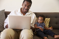 Grandfather And Grandson Sit On Sofa At Home Using Laptop - PhotoDune Item for Sale