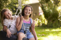 Portrait Of Two Girls Playing On Tire Swing In Garden