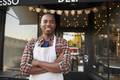 Black male business owner standing outside coffee shop