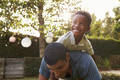 Young black boy playing on his dad's back in a garden