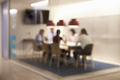 Corporate business team at table in a meeting room cubicle, defocussed