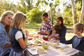 Two families having a picnic at a table in a park, close up