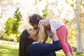Mixed race Asian mum kissing her young daughter in park - PhotoDune Item for Sale