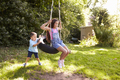 Brother Pushing Sister On Tire Swing In Garden - PhotoDune Item for Sale