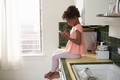Young Girl Sits In Kitchen And Plays With Mobile Phone - PhotoDune Item for Sale