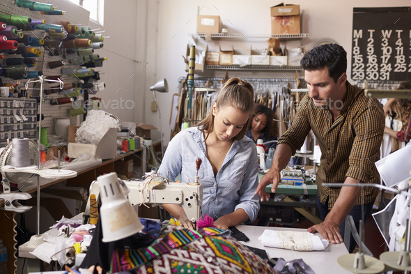Manager training machinist at a clothing design studio - Stock Photo - Images