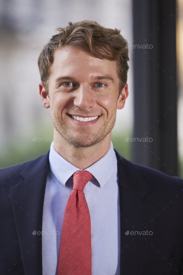 Young white businessman smiling, vertical portrait - Stock Photo - Images
