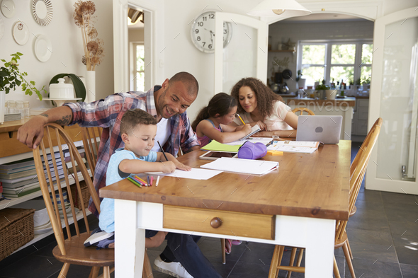 Parents Helping Children With Homework At Table - Stock Photo - Images