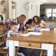 Parents Helping Children With Homework At Table - PhotoDune Item for Sale
