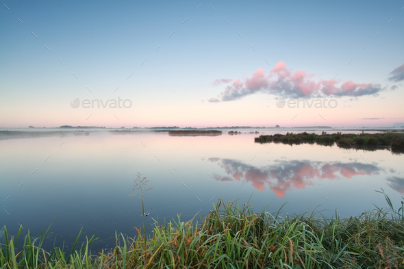 cloud reflection in lake at sunrise - Stock Photo - Images