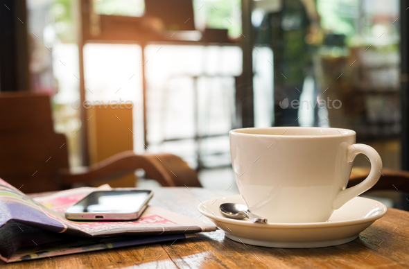Coffee on wooden table and a smart phone are on the newspaper. - Stock Photo - Images