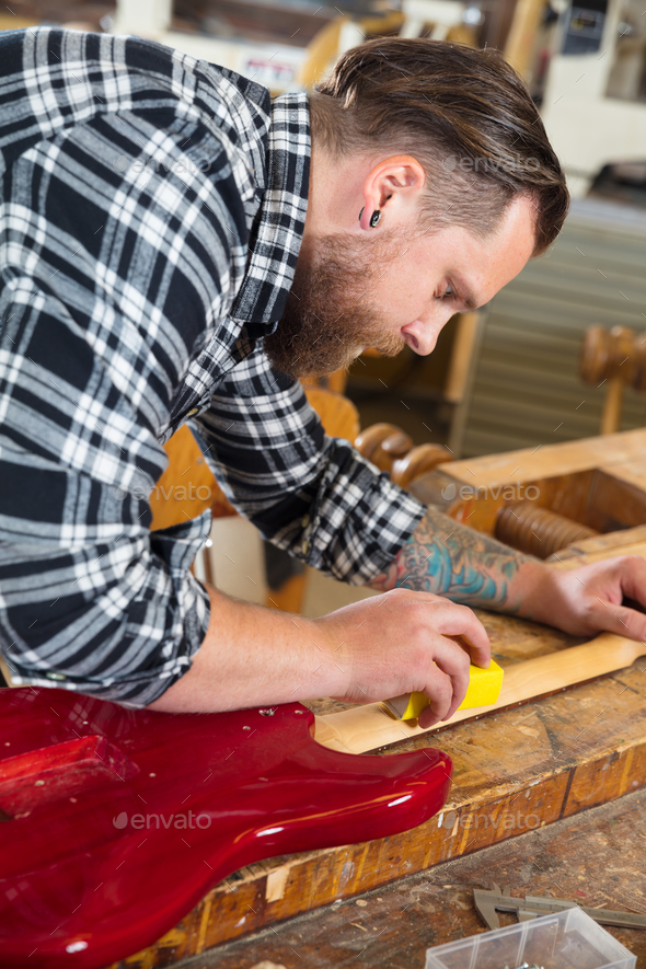 Craftsman sanding a guitar neck in wood at workshop - Stock Photo - Images