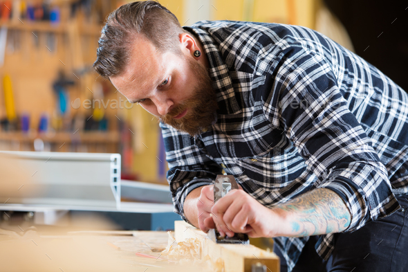 Carpenter works with plane on wood plank in workshop - Stock Photo - Images