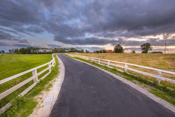 Curved road with white fences leading to village - Stock Photo - Images