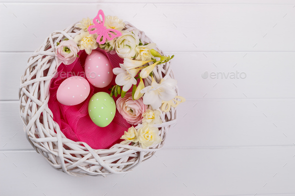 Basket of easter eggs with flowers - Stock Photo - Images