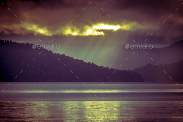 Sunrays falling through clouds over foggy mountain lake in vinta - Stock Photo - Images