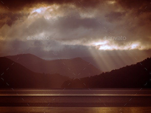Sunrays shining through clouds over foggy mountain lake in vinta - Stock Photo - Images