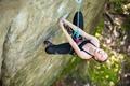 Young woman beginner climbing vertical cliff