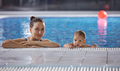 Young woman and little son resting poolside