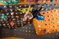 Expressive young woman bouldering in climbing gym