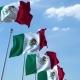 Row of Waving Flags of Mexico Agaist Blue Sky