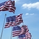 Row of Waving Flags of the United States Agaist Blue Sky