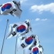 Row of Waving Flags of South Korea Agaist Blue Sky