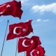 Row of Waving Flags of Turkey Agaist Blue Sky
