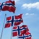 Row of Waving Flags of Norway Agaist Blue Sky