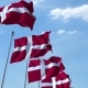 Row of Waving Flags of Denmark Agaist Blue Sky