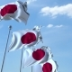 Row of Waving Flags of Japan Agaist Blue Sky