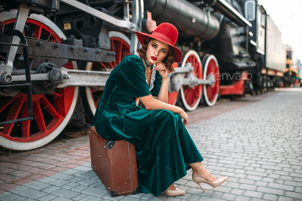 Woman sitting on suitcase against steam train - Stock Photo - Images