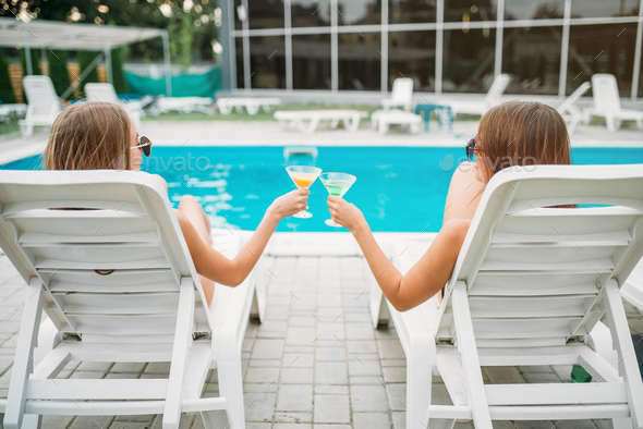 Two sexy girls lies on deck chairs near the pool - Stock Photo - Images
