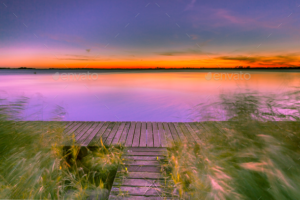 Long Exposure Image of Purple Sunset over Boardwalk on the shore - Stock Photo - Images