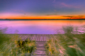 Long Exposure Image of Purple Sunset over Boardwalk on the shore