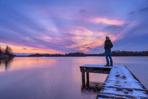 Man Looking at the Sunset From a Pier - Stock Photo - Images