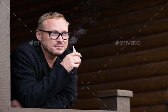 Caucasian man smoking modern hybrid cigarette device outdoor - Stock Photo - Images