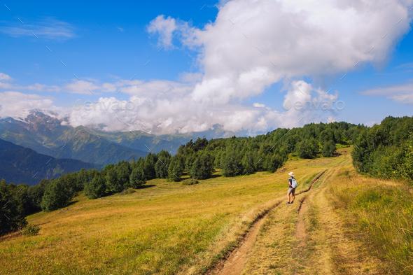 Woman hiker admiring mountains and meadows, Svaneti, Georgia - Stock Photo - Images