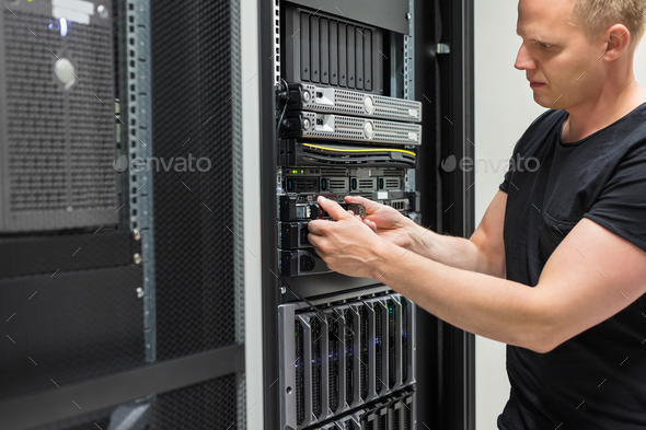 Male Technician Installing Hard Drive In Datacenter - Stock Photo - Images