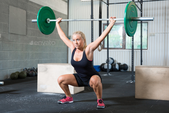 Determined Woman Lifting Weights In Health Club - Stock Photo - Images