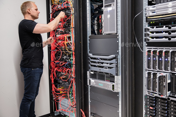 IT Technician Checking With Network Cables Connected To Servers - Stock Photo - Images